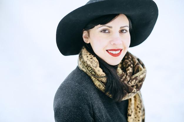 Mulher bonita no chapéu preto e jaqueta em pé e sorrindo e olhando feliz durante o dia.