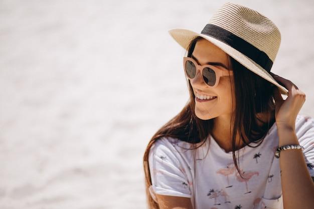 Mulher bonita no chapéu sentado na areia
