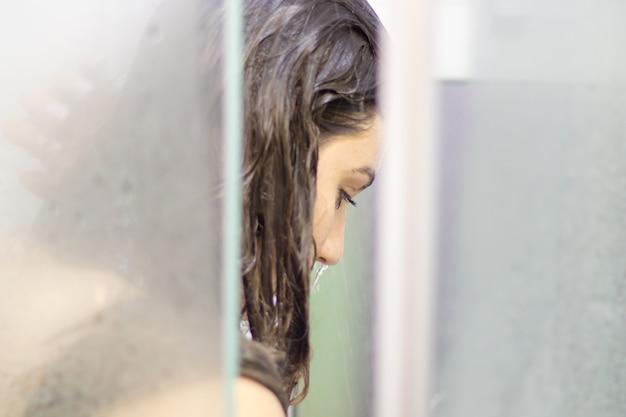 Mulher bonita no chuveiro por trás do vidro com gotas