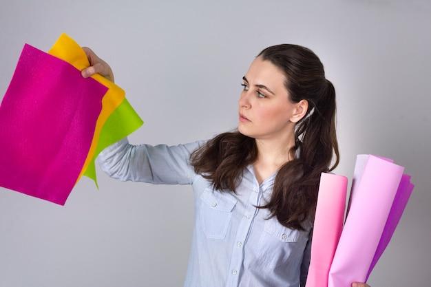 Mulher bonita no estúdio de artesanato escolhe materiais para o projeto diy. scrapbook, costura, feltro, passatempo quilting.