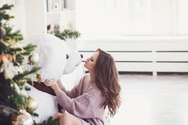 Mulher bonita no interior do natal beijando o ursinho de pelúcia