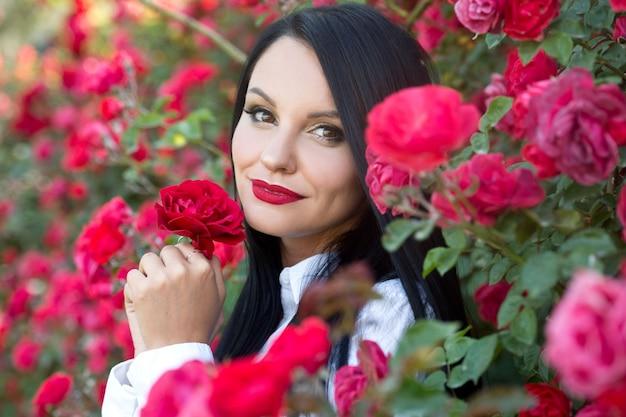 Mulher bonita no jardim de rosas. series. jardinagem.