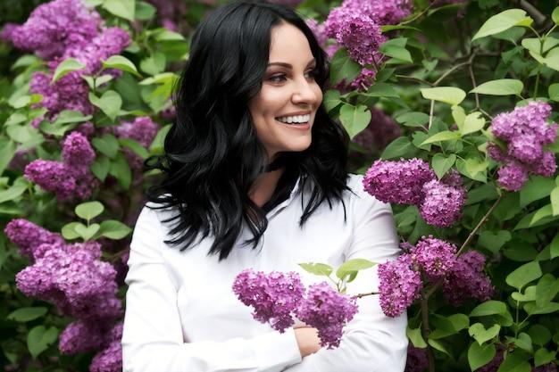 Mulher bonita no jardim lilás.