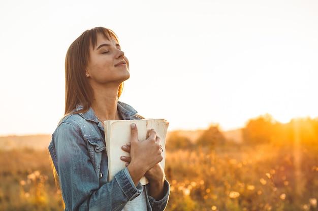 Mulher bonita no outono campo lendo um livro. a mulher sentada na grama, lendo um livro. descanse e leia. leitura ao ar livre.