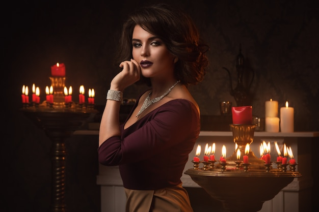 Mulher bonita no quarto com muitas velas