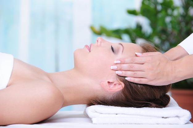 Mulher bonita no salão de beleza recebendo uma massagem facial