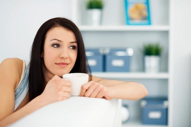 Mulher bonita no sofá com uma xícara de café