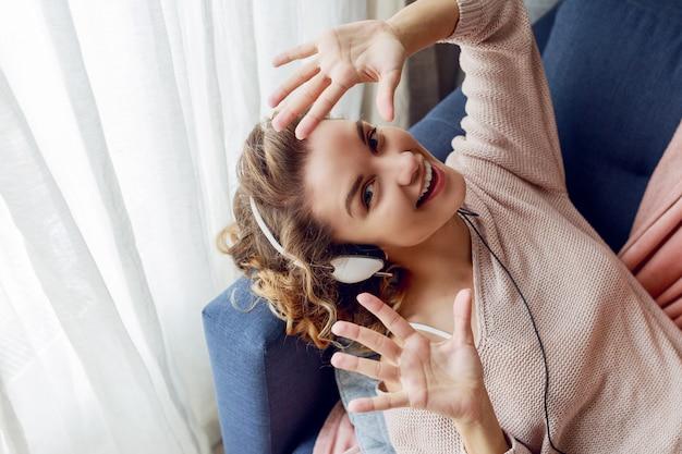 Mulher bonita no sofá ouvindo música