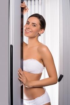Mulher bonita no solário. mulher jovem e atraente olhando para fora da cabine de bronzeamento e sorrindo