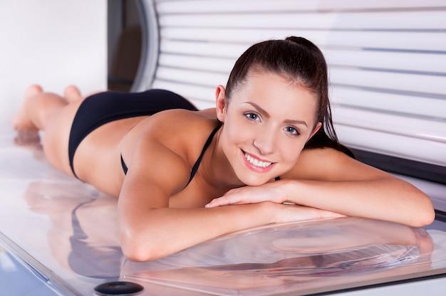Mulher bonita no solário. mulher jovem e atraente se bronzeando no solário e sorrindo para a câmera
