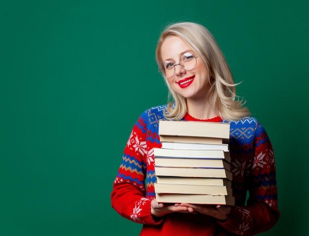 Mulher bonita no suéter de natal com um livro