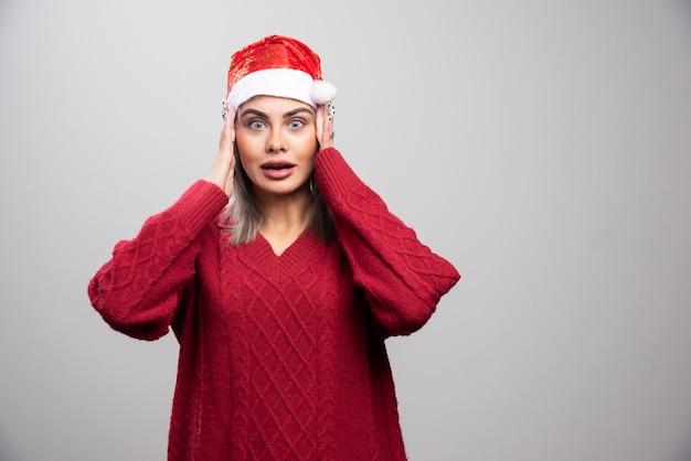 Mulher bonita no suéter vermelho esqueceu seus presentes.