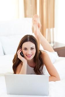 Mulher bonita no telefone usando seu laptop deitado na cama