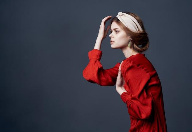 Mulher bonita no turbante de etnia luxo vestido vermelho na parede escura de enfeites de cabeça.