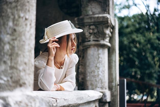 Mulher bonita no vestido branco ao ar livre com edifício antigo atrás