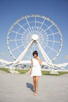 Mulher bonita no vestido branco de pé e olhando no parque com roda gigante