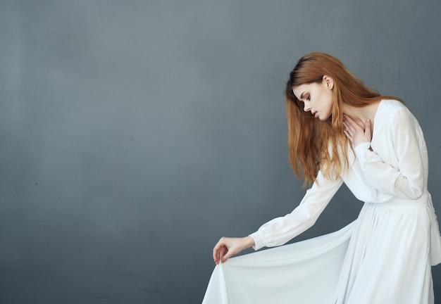 Mulher bonita no vestido branco glamour desempenho de estúdio. foto de alta qualidade