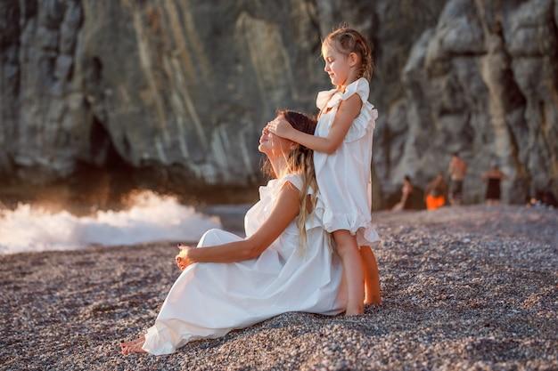 Mulher bonita no vestido branco sentado enquanto sua filha fechar os olhos na beira-mar durante o pôr do sol.