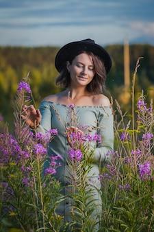 Mulher bonita no vestido de beleza, chapéu preto com um grande buquê com flores roxas ri e caminhar ao ar livre em um prado durante o pôr do sol. conceito de caminhada ao vivo.