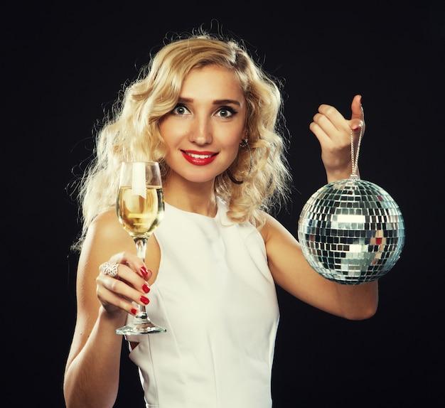 Mulher bonita no vestido de noite com vinho e bola de discoteca
