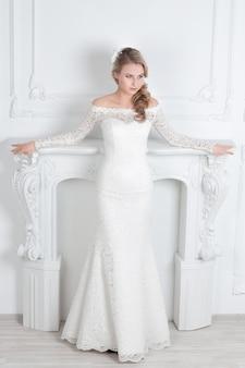 Mulher bonita no vestido de noiva em pé perto da lareira decorativa. feriados e eventos