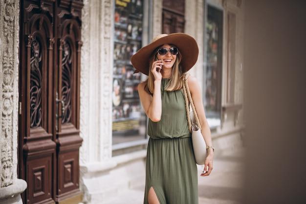 Mulher bonita no vestido e chapéu falando ao telefone