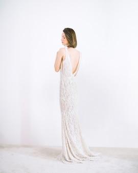 Mulher bonita no vestido longo branco em pé e pensando na sala com branco