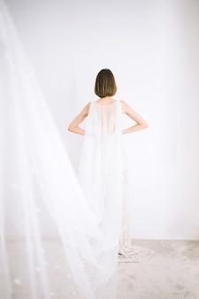 Mulher bonita no vestido longo branco em pé na sala com paredes brancas
