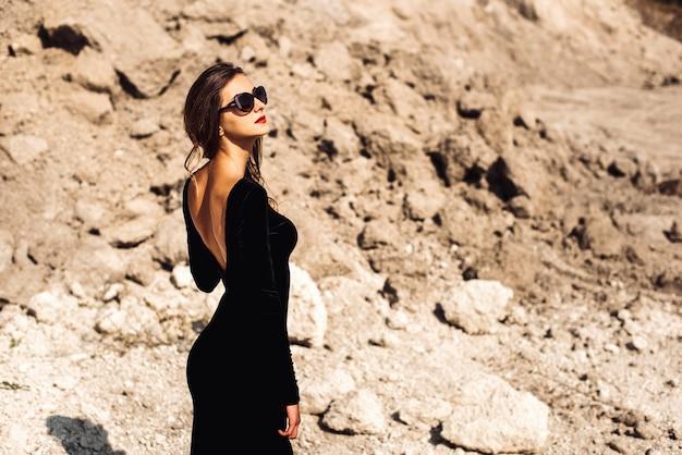 Mulher bonita no vestido preto longo caminhando ao ar livre