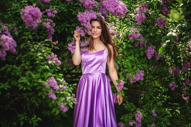 Mulher bonita no vestido roxo posando perto das árvores lilás