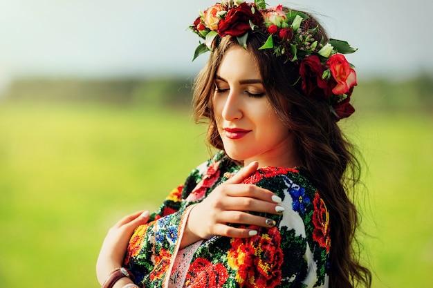 Mulher bonita no vestido tradicional ucraniano colorido segurando