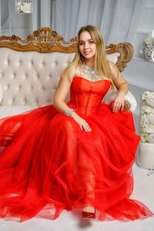Mulher bonita no vestido vermelho sentado no sofá