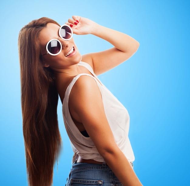 Mulher bonita nos óculos de sol que sorri sobre o ombro Foto gratuita