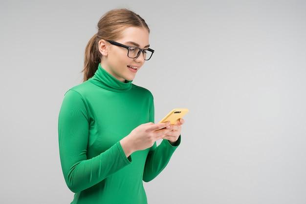 Mulher bonita nos óculos mantém seu iphone e lê uma mensagem