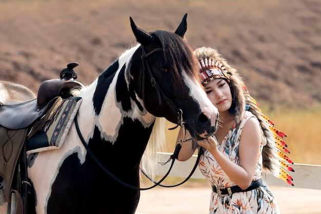 Mulher bonita nova, beleza, composição tribal étnica, desenhos na cara, bordos vermelhos, brincos, estilo boêmio da hippie e cavalo.