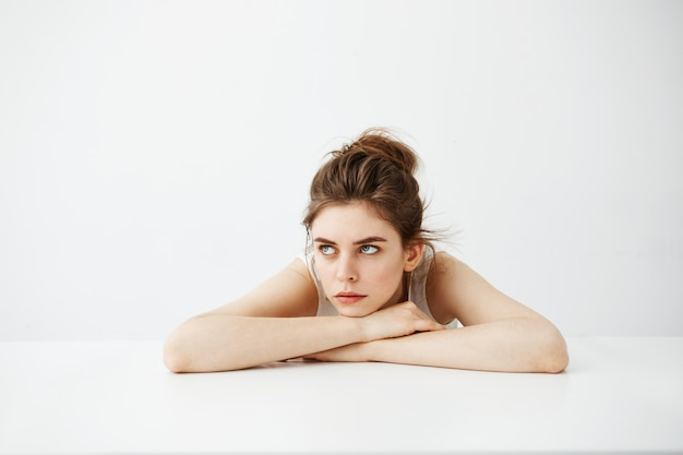 Mulher bonita nova cansada entediada com bolo que pensa sonhando o encontro na tabela sobre o fundo branco.