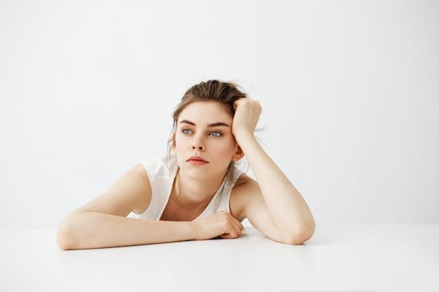 Mulher bonita nova cansada entediada com bolo que pensa sonhando sentado à mesa sobre fundo branco.