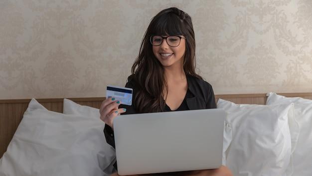 Mulher bonita nova com cartão e laptop de crédito, conceito em linha da compra.