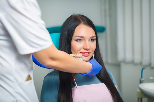 Mulher bonita nova com os dentes brancos bonitos que sentam-se em uma cadeira dental.