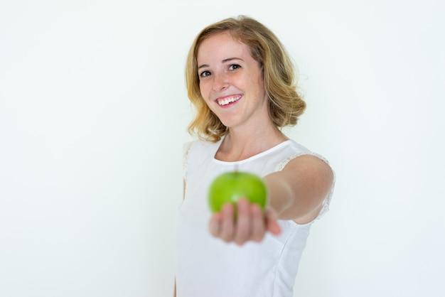 Mulher bonita nova de sorriso que oferece a maçã verde borrada