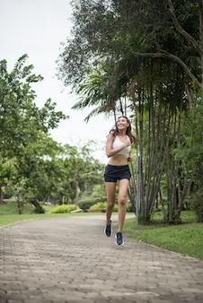 Mulher bonita nova do esporte que corre no parque. conceito de saúde e esporte.