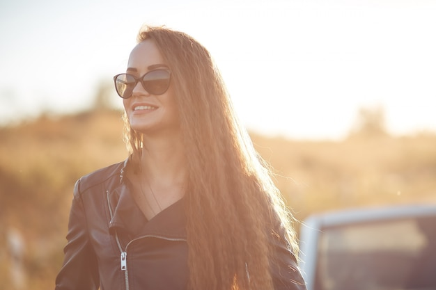 Mulher bonita nova do negócio nos óculos de sol contra o céu azul no por do sol.