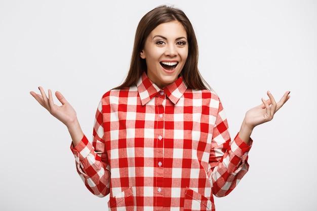 Mulher bonita nova na camisa vermelha e branca da verificação