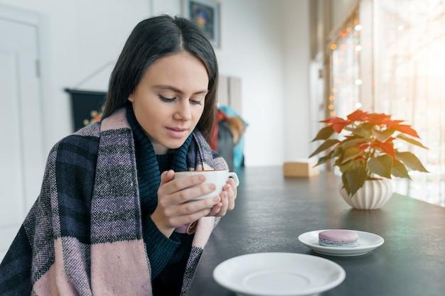 Mulher bonita nova na estação do inverno que aquece-se com café quente e a cobertura morna que senta-se na cafetaria perto da janela.