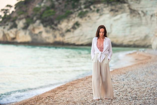 Mulher bonita nova na praia tropical branca.