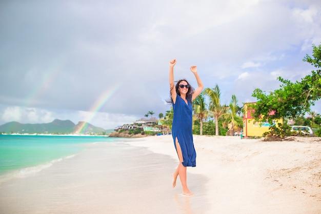 Mulher bonita nova no litoral tropical. garota feliz relaxante na praia tropical de areia branca