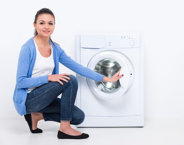 Mulher bonita nova perto da máquina de lavar.