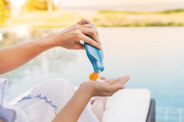 Mulher bonita nova que aplica a proteção solar ou a loção para bronzear em seu corpo para a proteção solar da pele na piscina, conceito das férias de verão.