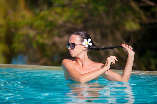 Mulher bonita nova que aprecia a piscina quieta luxuosa