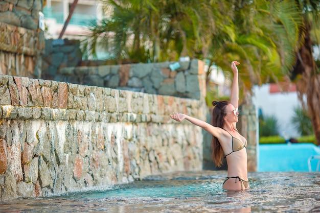 Mulher bonita nova que aprecia a piscina quieta luxuosa.